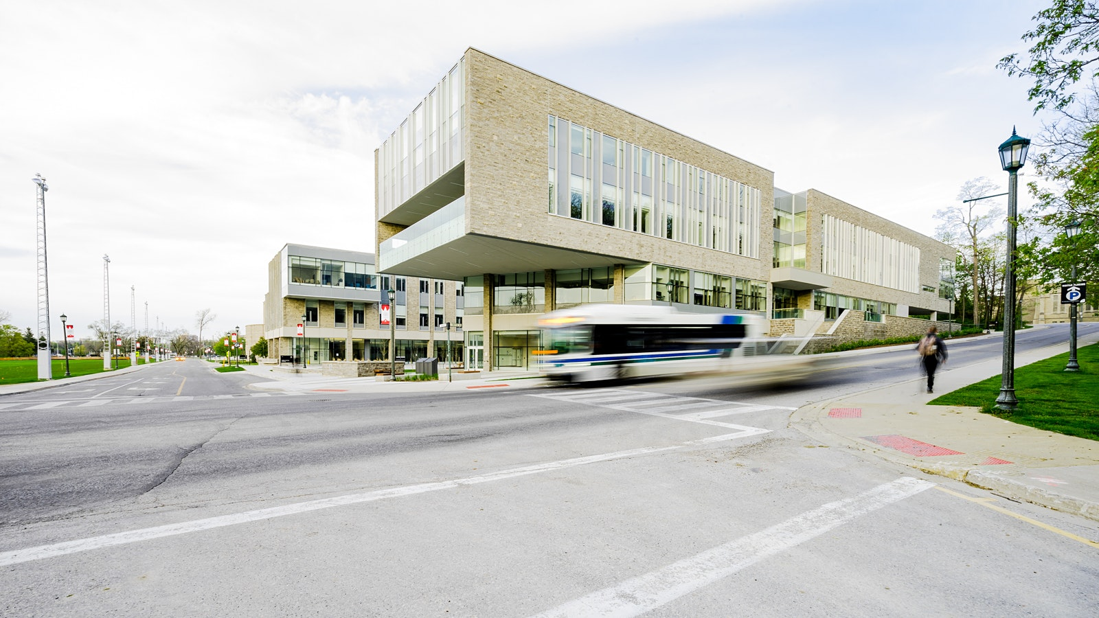 Exterior of Fims & nursing building as bus, car, and person go by in London Ontario